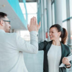 Bem-estar no trabalho: funcionários felizes se cumprimentando